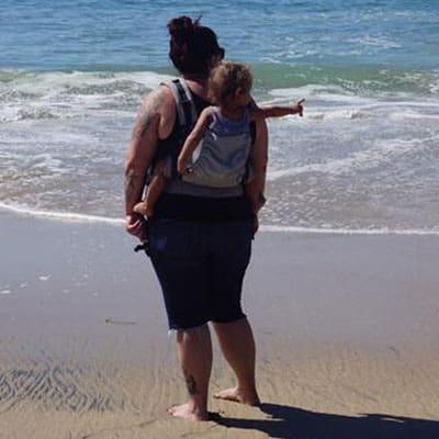 Hannah with Jude at the beach in a tula Coast